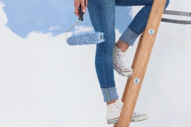 Woman holding paint roller on ladder against half painted wall